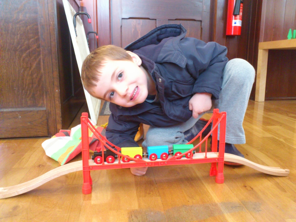 Young visitor playing with toy train in Museum